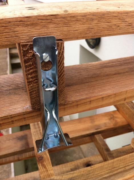 Man befestigt die Vorrichtung mit einem Schrauben oder Nagel an gewünschtem Ort und die Klemme hält jeden Topf.