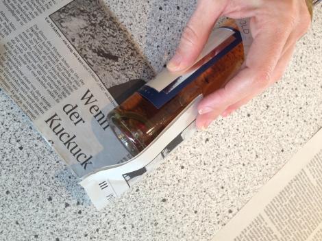 Mit der offenen Seite zum Flaschenboden um die Flasche gewickelt. Das Zeitungspapier muss so weit überstehen, dass es die Wölbung abdeckt.