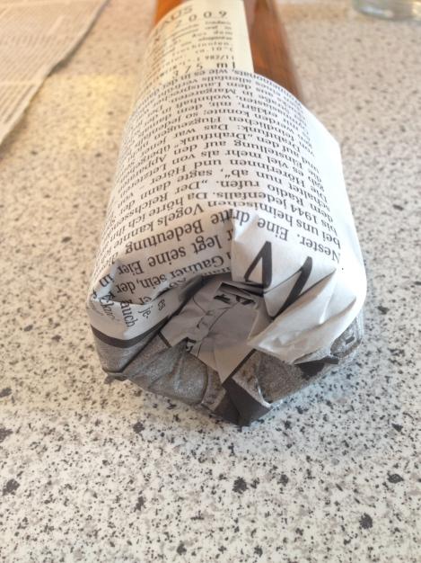Also Papier rum wickeln und das Ende in die Wölbung falten, von der Flasche ziehen ...